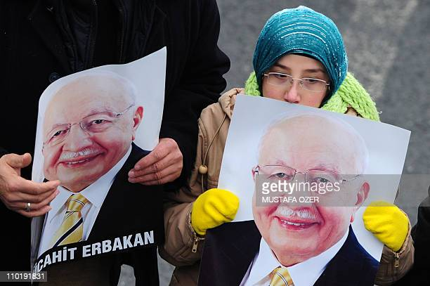 Mourner hold pictures of former Turkish Prime Minister Necmettin Erbakan as tens of thousands of people gather on March 1 2011 in Istanbul for the...