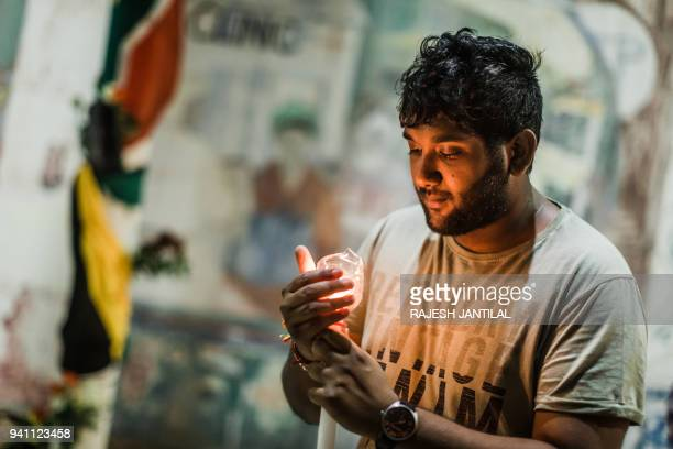 A mourner holds a candle as he stands near the Old Durban Prison's Human Rights wall as he and others pay their respect to the late South African...