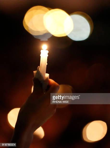 A mourner holds a candle during a candlelight vigil for victims of the Marjory Stoneman Douglas High School shooting in Parkland Florida on February...