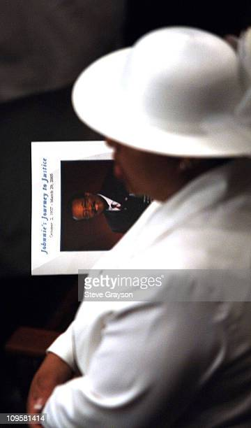A mourner holds a program during the funeral service for Johnnie Cochran at the West Angeles Cathedral in Los Angeles California April 6 2005