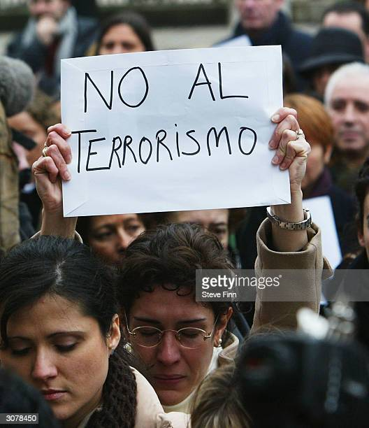A mourner holds a sign aloft during a minute's silence held to honour the victims of the Madrid train bombings outside the Spanish Embassy on March...