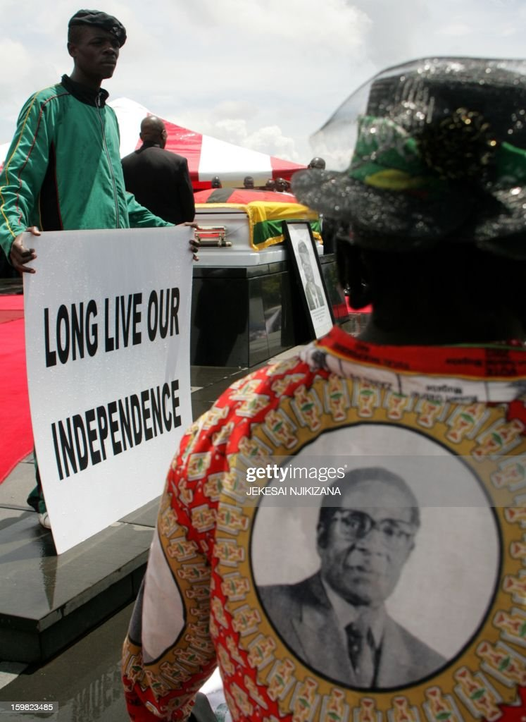 A mourner holds a sign reading 'Long Live our Independence' as another wears regalia bearing the face of Zimbabwe President Robert Mugabe during the burial of the late vice-president John Landa Nkomo at the National Heroes Acre, in Harare, on January 21, 2013. President Mugabe called for a peaceful election. Nkomo, 78, died at St. Anne's hospital in Harare on January 17. Responsible for overseeing financial, economic and environmental policy Nkomo, a former speaker of parliament, was seen as loyal to Mugabe. AFP PHOTO / Jekesai Njikizana