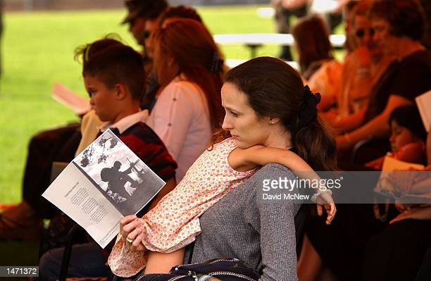 A mourner holds a sleeping girl during a memorial service for slain US Marine Lance Cpl Antonio J Sledd October 11 2002 at Camp Pendleton California...