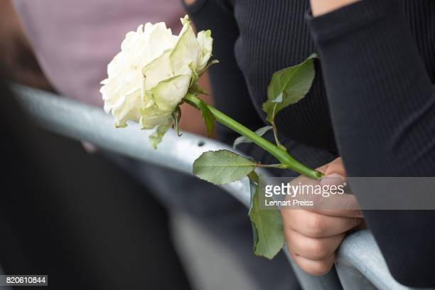 A mourner holds a white rose at an event to commemorate the first anniversary of the shooting spree that one year ago left ten people dead including...