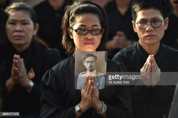 TOPSHOT A mourner holds an image of the late Thai King Bhumibol Adulyadej as she waits for his funeral procession to take place in Bangkok on October...