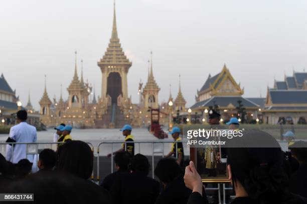 A mourner holds an image of the late Thai King Bhumibol Adulyadej as she takes a photo in front of the Royal Crematorium before the royal cremation...