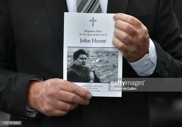 A mourner holds an order of service as the funeral takes place of former SDLP leader and Nobel Peace Prize winner John Hume at St Eugene's cathedral...