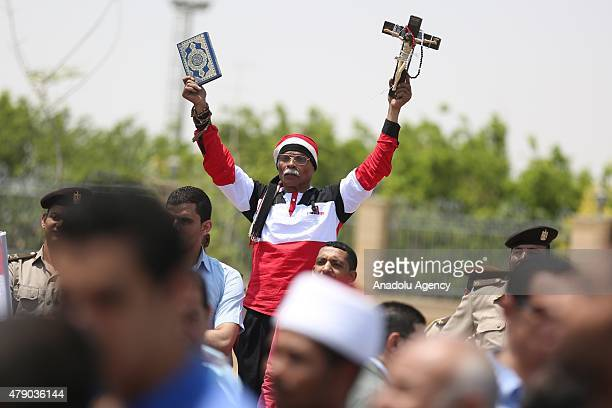 A mourner holds up a copy of Islam's holy book Quran and Christian Cross outside the Tantawi Mosque during the funeral of Egyptian ProsecutorGeneral...