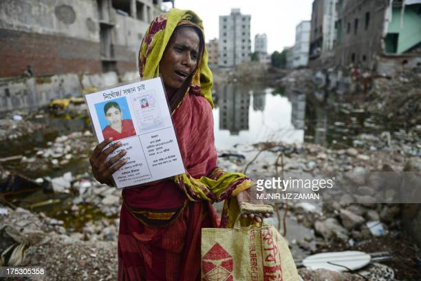 Mourner holds up a portrait of her missing relative , presumed dead following the April 24 Rana Plaza garment building collapse, and a bone fragment...