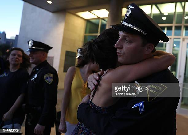 Mourner hugs a Fayetteville, North Carolina police officer in front of the Dallas Police department headquarters on July 12, 2016 in Dallas, Texas....