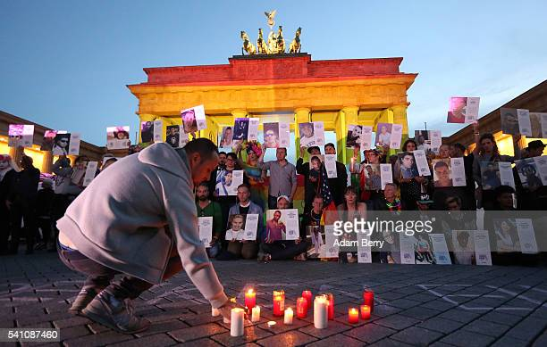 A mourner in front of a LGBT rainbow flag at Brandenburg Gate lights a memorial candle as others stand with photographs of victims of a shooting at...