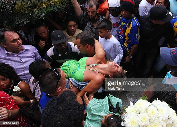 A mourner is carried out after fainting at the funeral of dancer Douglas Rafael da Silva who was shot and killed on April 24 2014 in Rio de Janeiro...