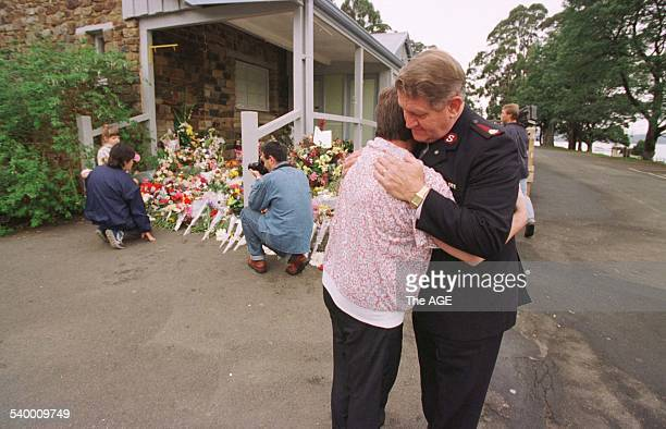 A mourner is comforted by a Salvation Army officer as others leave flowers on the steps of the Broad Arrow Cafe at the Port Arthur historic site...
