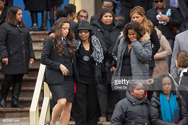 A mourner is helped down the steps of the church after the funeral service of Rosemarie 'Kim' Junor the woman who was stabbed in the PATH Shoppers...