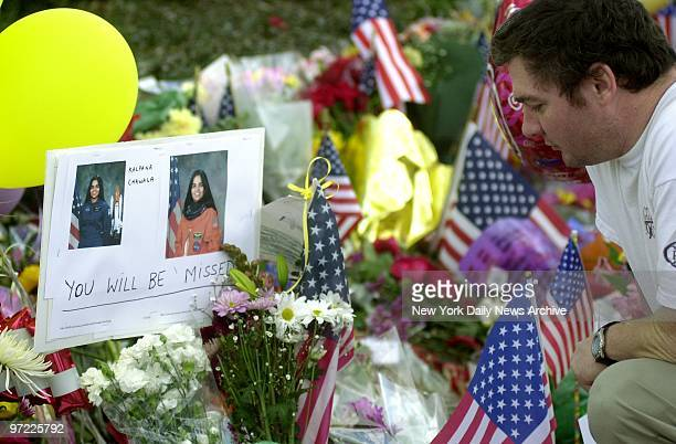 A mourner kneels before photos of astronaut Kalpana Chawla at a makeshift memorial at the Johnson Space Center in Houston to the seven crewmembers...