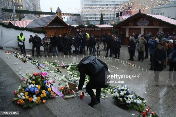 A mourner lays a candle at a memorial to victims following its inauguration at the site of the 2016 Christmas market terror attack at...