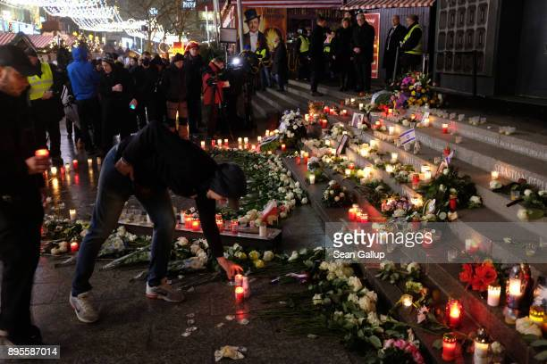 A mourner lays a candle at a memorial to victims following the memorial's inauguration at the site of the 2016 Christmas market terror attack at...