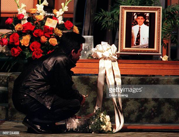 Mourner lays flowers beneath a photograph of Michael Rebaza, during the memorial service for Rebaza , who was killed by a ambulance commandeered by a...