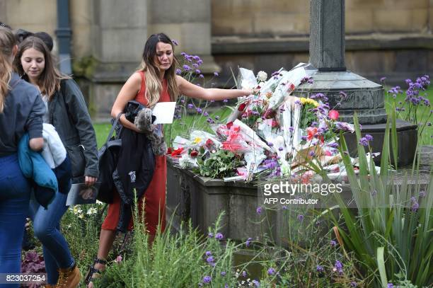 A mourner lays flowers outside the church following the funeral of Manchester Arena Bombing victim SaffieRose Roussos at Manchester Cathedral in...