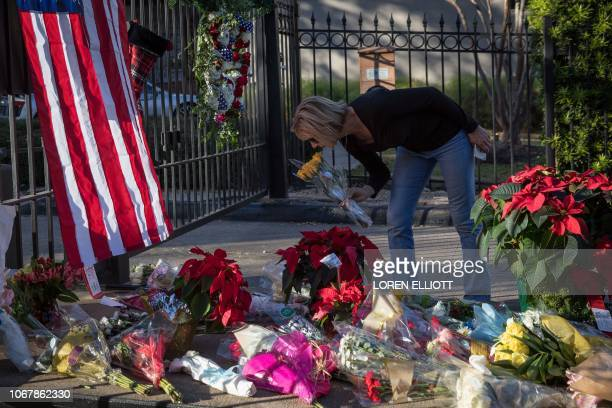 A mourner leaves flowers at a makeshift memorial in tribute to former US President George H W Bush outside a gated community where Bush lived in...