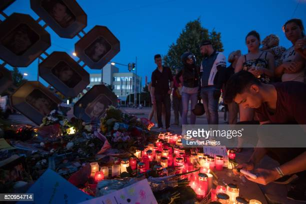 A mourner lights a candle at a memorial to commemorate the victims of the shooting spree that one year ago left ten people dead including the shooter...