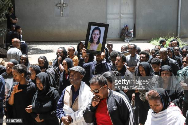 A mourner of a victim of the crashed accident of Ethiopian Airlines holds a portrait during the mass funeral at Holy Trinity Cathedral in Addis Ababa...