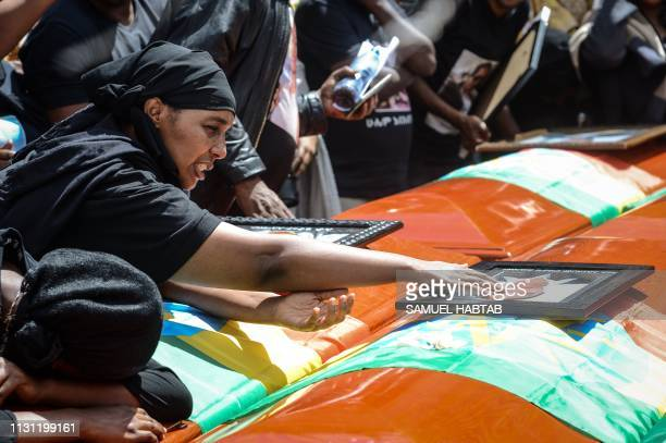 TOPSHOT A mourner of victims of the crashed accident of Ethiopian Airlines touches a portrait on a coffin during the mass funeral at Holy Trinity...