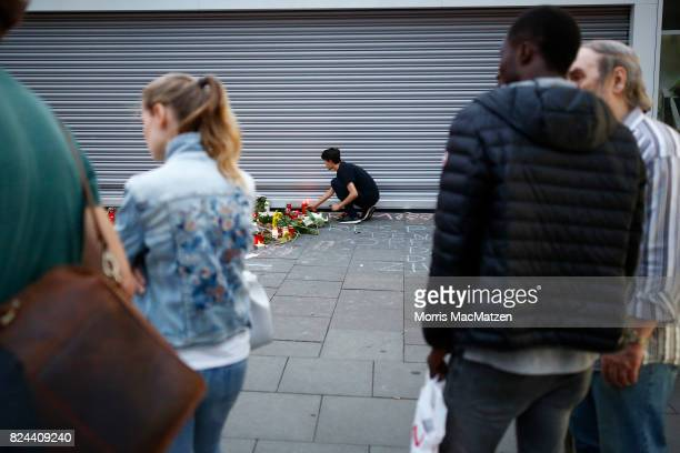 A mourner places a candle light outside the Edeka supermarket where on Friday Ahmad A killed one and injured six people with a knife on July 28 2017...