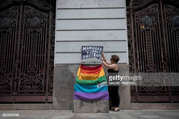 TOPSHOT A mourner places a sign and a rainbow flag outside Rio de Janeiro's Municipal Chamber during the funeral of slain Brazilian councilwoman and...
