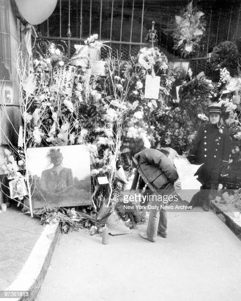 Mourner places bouquet among other items including an oil painting arrayed outside the Dakota apartments on 72d St and Central Park West where John...