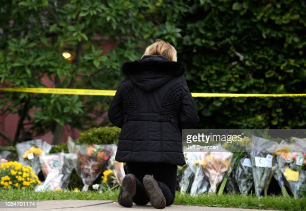 A mourner prays after laying flowers at the site of the mass shooting that killed 11 people and wounded 6 at the Tree Of Life Synagogue on October 28...