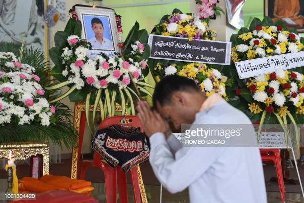 TOPSHOT A mourner prays in front of a portrait of 13yearold Muay Thai boxer Anucha Tasako next to his coffin during a funeral at a Buddhist temple in...