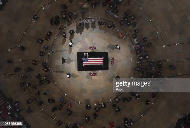 A mourner puts a hand on the flagdraped casket of the late former President George HW Bush as he lies in state in the Capitol Rotunda on December 4...