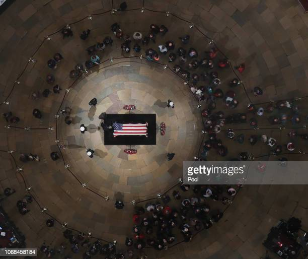 A mourner puts a hand on the flagdraped casket of the late former President George HW Bush as he lies in state in the US Capitol Rotunda on December...