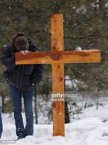 A mourner puts her head on a wooden cross on Highway 395 near Burns Oregon on January 29 at the location where Robert 'LaVoy' Finicum was shot dead...