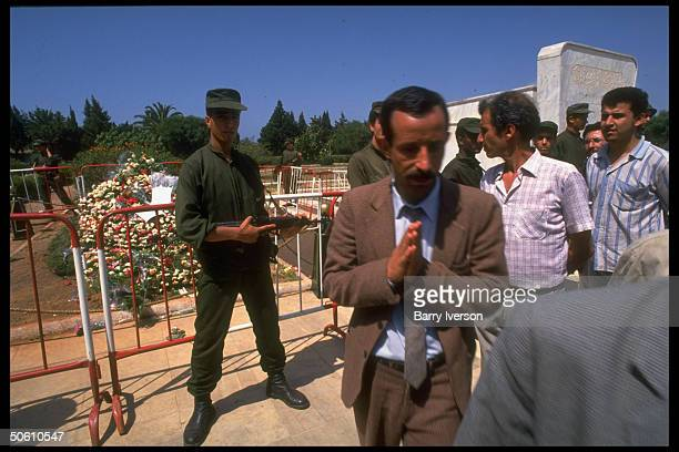 Mourner raising hand in show of respect by security teamringed grave of assassinated Pres Mohammed Boudiaf at cemetery in Algiers Algeria