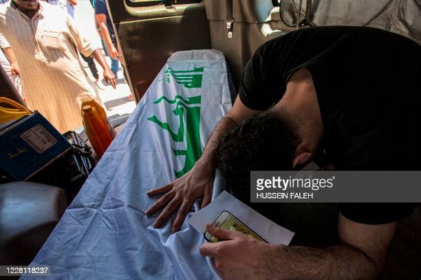 Mourner reacts as he sits in the back of a vehicle by the Iraqi-flag draped coffin of slain activist Riham Yaaqub during her funeral in the centre of...