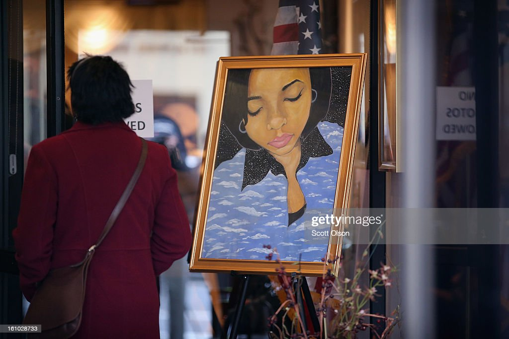A mourner stands next to a painting of 15-year-old Hadiya Pendleton, placed at the entrance of the Calahan Funeral Home during her wake on February 8, 2013, in Chicago, Illinois. Hadiya was killed when a gunman opened fire on her and some friends as they stood under a shelter on a warm rainy afternoon in a park about a mile from President Obama's Chicago home. First lady Michelle Obama is expected to attend tomorrow's funeral with senior White House adviser Valerie Jarrett and Education Secretary Arne Duncan.
