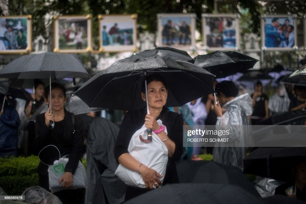 TOPSHOT - A mourner stands under an umbrella during a heavy rain shower in front of the cremation grounds where the body of late Thai King Bhumibol Adulyadej's body was taken to be cremated in Bangkok on October 26, 2017. A sea of black-clad mourners massed across Bangkok's historic heart early on October 26 as funeral rituals began for King Bhumibol Adulyadej, a revered monarch whose passing after a seven-decade reign has left Thailand bereft of its only unifying figure. /