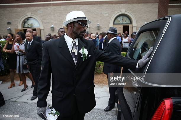 A mourner touches the back of the hearse carrying the casket of Ethel Lance who was one of nine victims of a mass shooting at the Emanuel African...