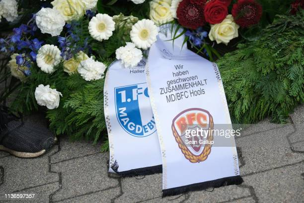 A mourner waiting outside Michaelis cemetery stands next to a wreath with ribbons from the Magdeburg and Dresden football hooligan clubs prior to the...