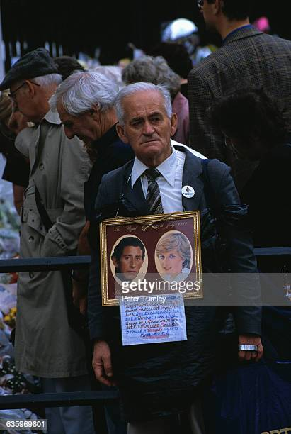A mourner wears a picture with the photographs of Charles Prince of Wales and Diana Princess of Wales soon after the tragic automobile accident on...