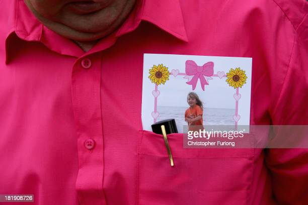 A mourner wears a pink shirt and tucks the order of service in his shirt pocket during the funeral service of murdered schoolgirl April Jones at St...