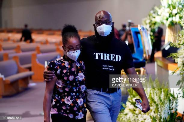 """Mourner wears a t-shirt reading """"tired"""" after passing by the casket of George Floyd during a public viewing for Floyd at the Fountain of Praise..."""