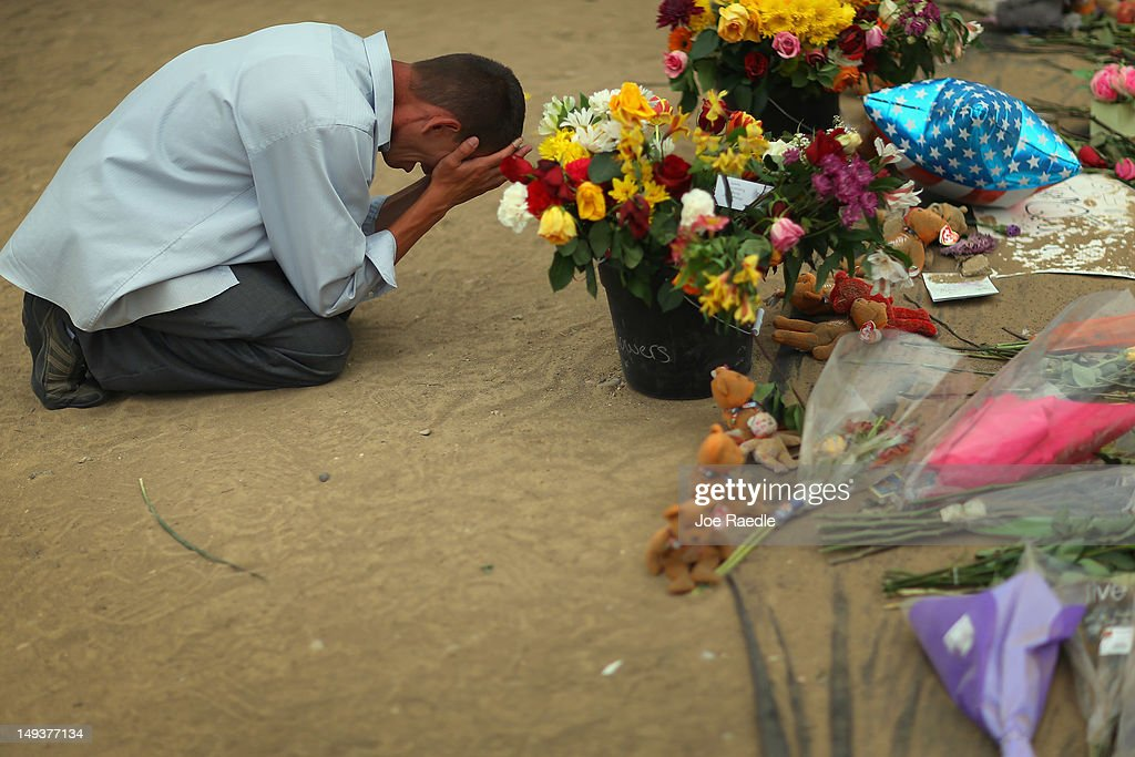 A mourner who wish to remain unidentified cries at a memorial setup across the street from the Century 16 movie theatre on July 27, 2012 in Aurora, Colorado. Twenty-four-year-old James Holmes is suspected of killing 12 and injuring 58 others July 20 during a shooting rampage at a screening of 'The Dark Knight Rises' in Aurora, Colorado.