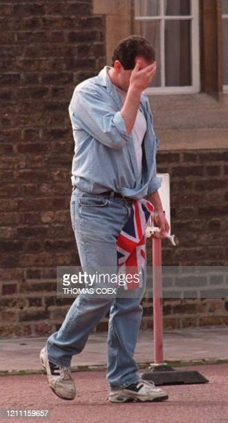 Mourner, with a Union flag tucked into his jeans, puts a hand to his face to hide his grief after placing flowers at St. James's Palace here 01...