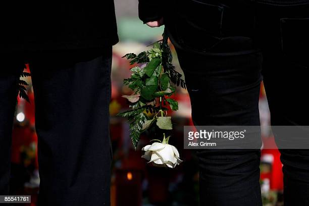 A mourner with a white rose stands in front of flowers and candles outside Albertville high school on March 21 2009 in Winnenden near Stuttgart...