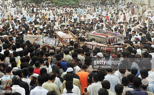 Mourners acrry coffins as they attend the funeral of local gangster Abdul Rehman, known as Rehman Dakait and his aides in Karachi on August 10, 2009....