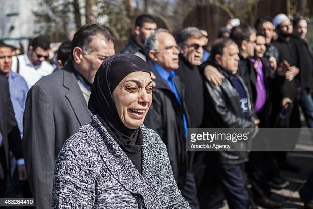 Mourners and people from the Islamic Association of Raleigh attend a service at a nearby soccer field February 12 2015 in Raleigh North Carolina...