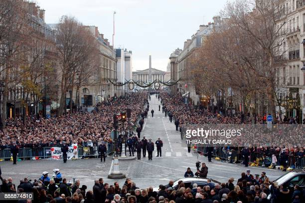 Mourners are gathered in front of the La Madeleine Church ahead of the funeral ceremony in tribute to the late French singer Johnny Hallyday in Paris...